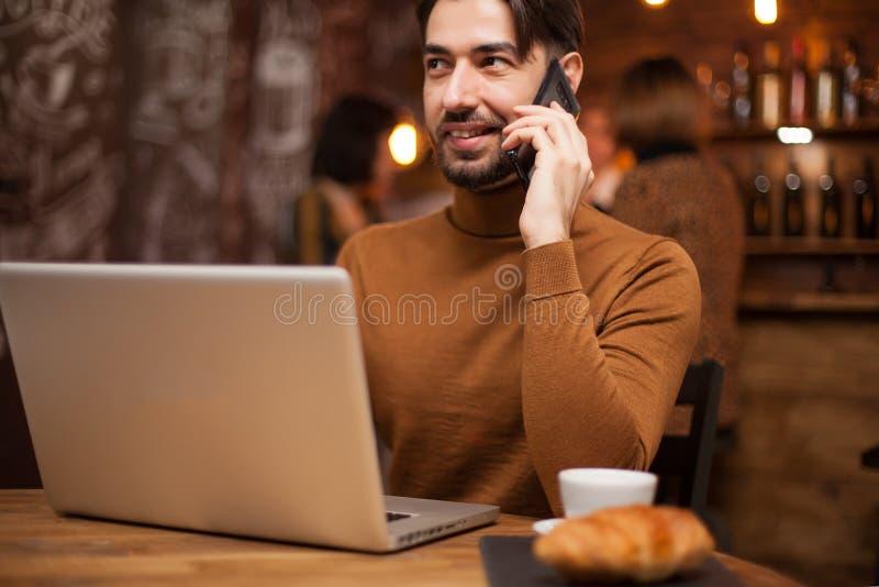Uitvoerende zakenman die op de telefoon spreken terwijl het werken aan zijn laptop in een koffiewinkel stock foto