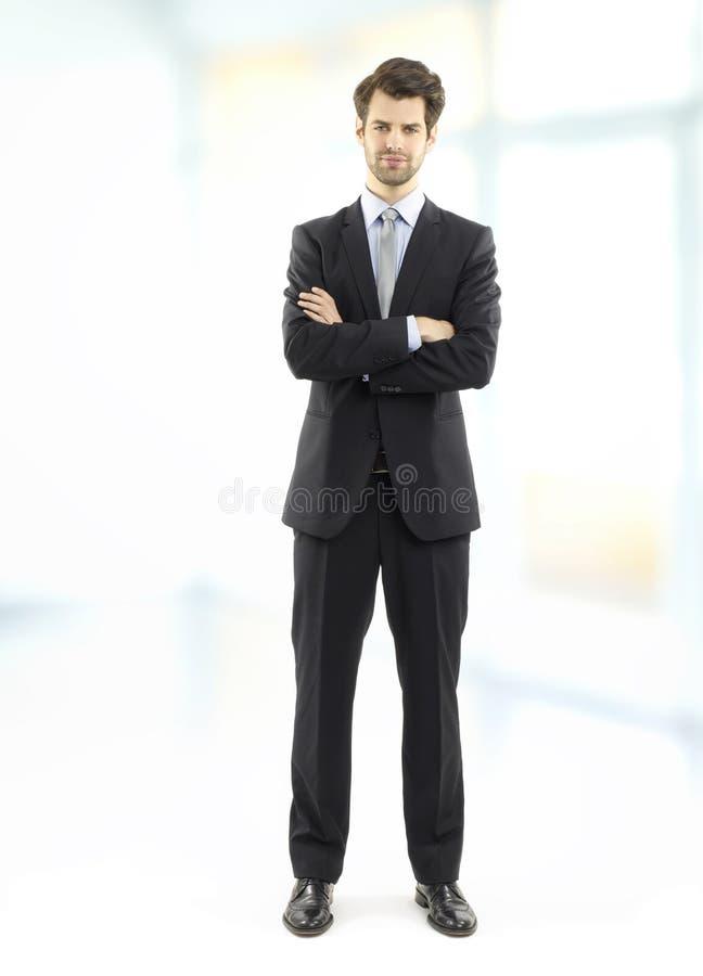 Uitvoerende zakenman die zich op kantoor bevinden stock afbeelding