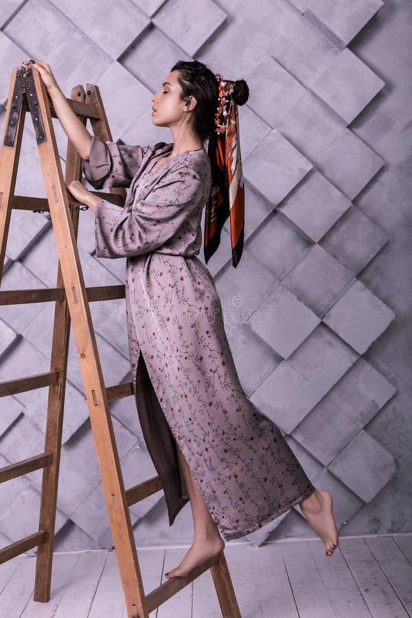 Ujmujący poser jest ubranym smokingową pozycję na drabinie podczas pracownianej strzelaniny zdjęcie stock