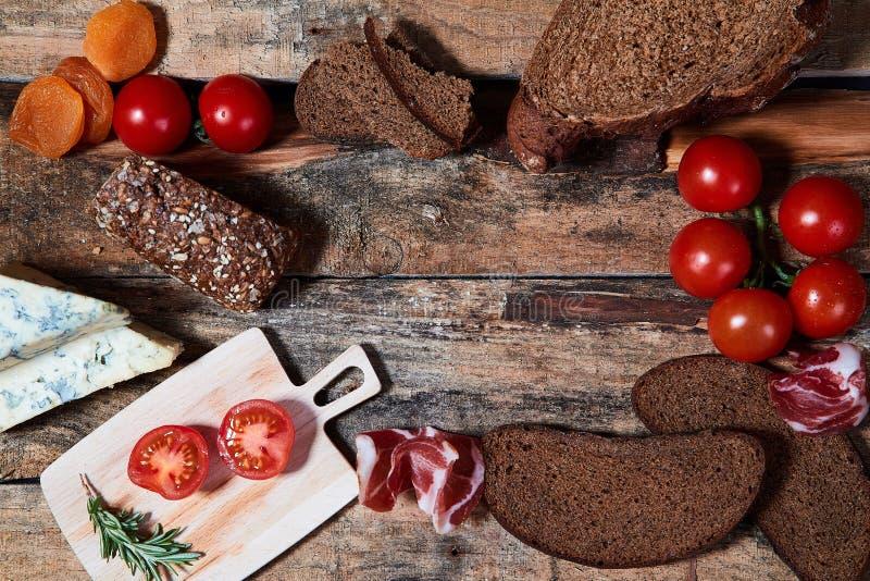 Układ asortowany smakosz przekąsza z chlebem i błękitnymi pomidorami na drewnianej powierzchni sera i dojrzałych fotografia stock