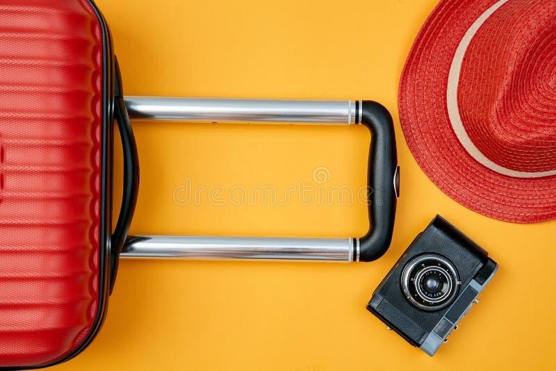 Układ czerwona walizka i kapelusz obok retro kamery na jaskrawym żółtym tle Blogging lub blogger pojęcie zdjęcia royalty free
