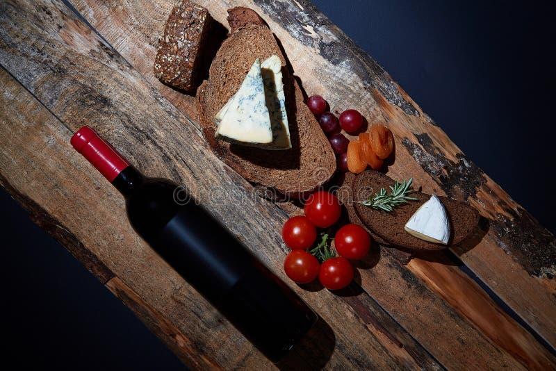 Układ wyśmienicie smakosz przekąsza z chlebem, ser i owoc na drewnianych deskach z butelką czerwone wino obraz royalty free