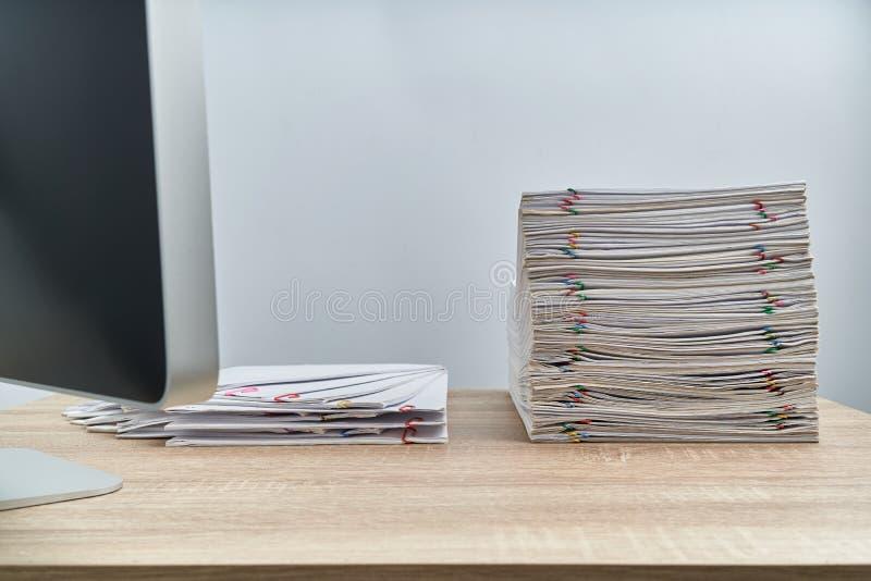 Układa palowego przeciążenie papierkowej roboty raport i komputer na drewnianym stole zdjęcie royalty free