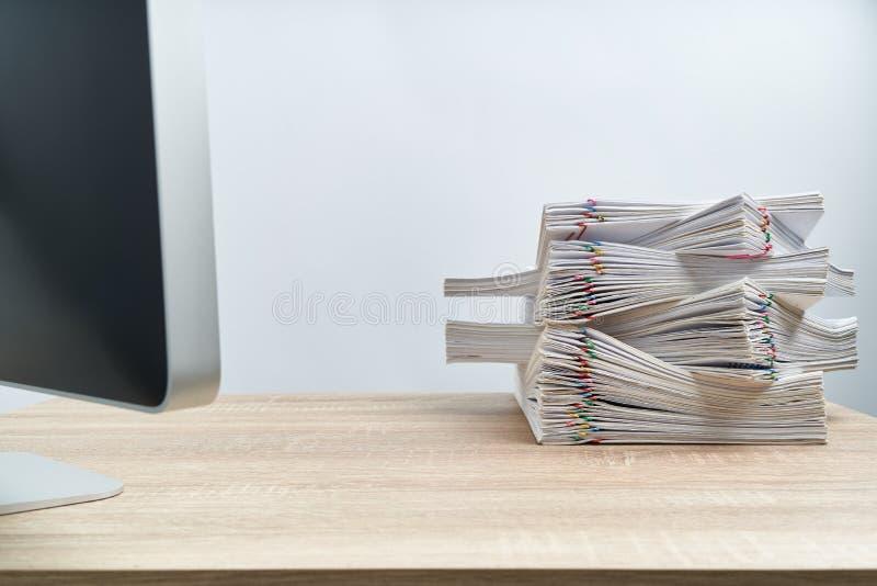 Układa papierkowej roboty przeciążenia komputer na drewnianym stole i raport obraz royalty free