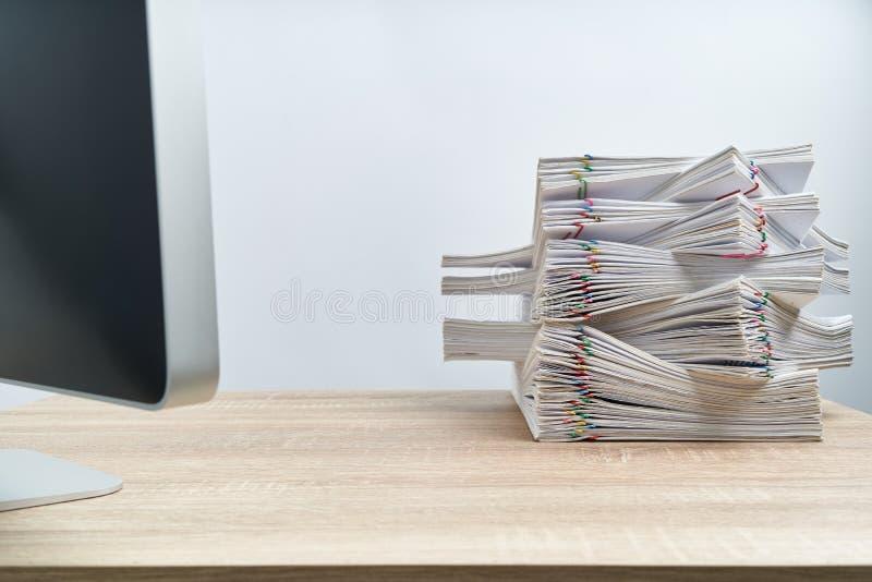Układa przeciążenie papierkowej roboty komputer na drewnianym stole i raport zdjęcia stock