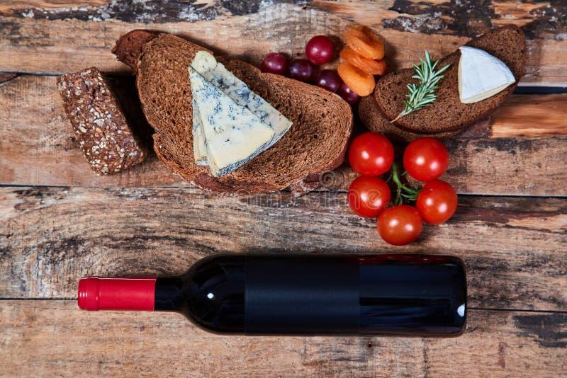 Uk?ad wy?mienicie smakosz przek?sza z chlebem, ser i owoc na drewnianych deskach z butelk? czerwone wino fotografia stock