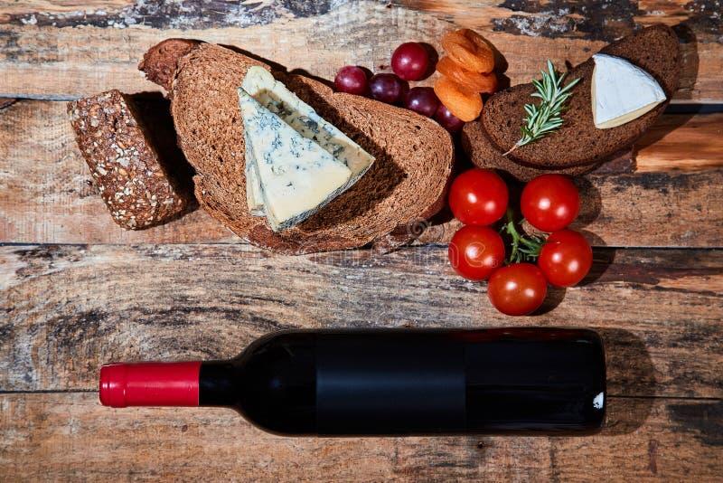 Uk?ad wy?mienicie smakosz przek?sza z chlebem, ser i owoc na drewnianych deskach z butelk? czerwone wino zdjęcia royalty free