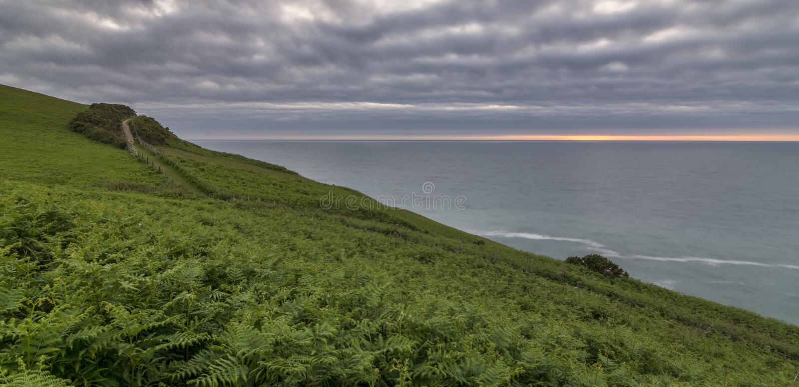 UK coastal path view, with a cloudy sky and a thin sunset. Welsh coastal path, near Aberaeron, Caeredigion, at sunset stock photography