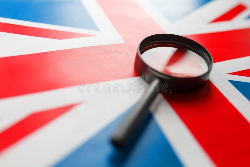 UK-flagga som ser till och med ett förstoringsglas Studien av historien och kulturen av folket av det stora landet av England royaltyfria bilder