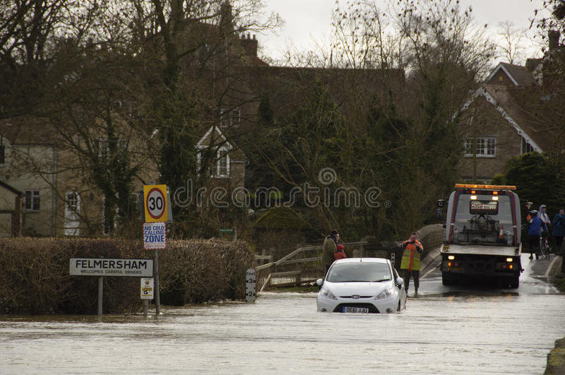 UK 2014 Floods Felmersham England UK. Flooding on a road in Felmersham Bedfordshire England UK next to the Great River Ouse. Mechanics attempt to rescue a stock images