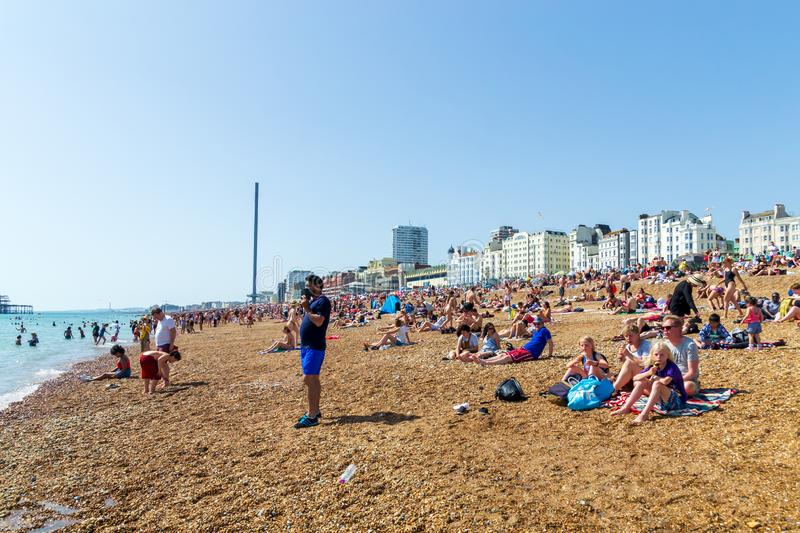 UK June 29th, 2019 Brighton beach, Brighton and Hove, East Sussex, England. Thousands of people relax on the sun. Architecture, heat, blue, pier, britain stock images