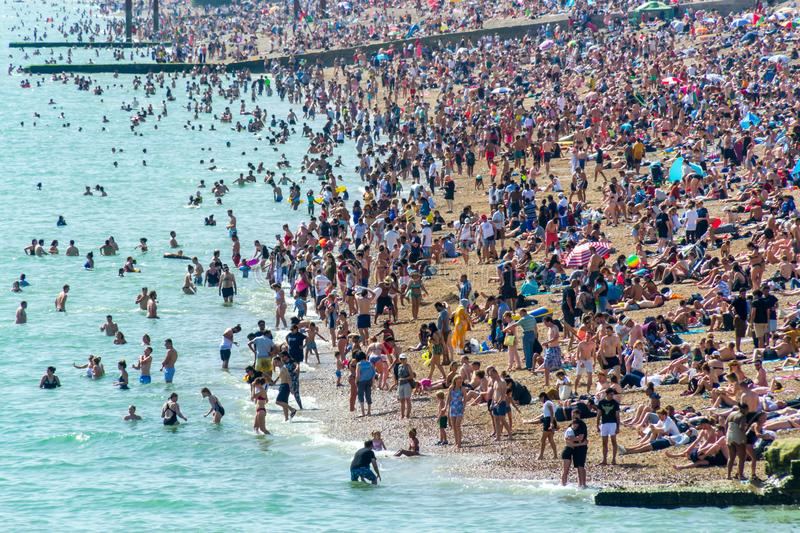 UK June 29th, 2019 Brighton beach, Brighton and Hove, East Sussex, England. Thousands of people relax on the sun. Architecture, heat, blue, pier, britain royalty free stock image