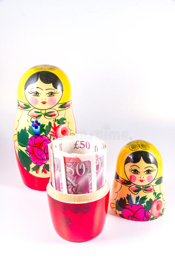 UK Money in Russia hands - £50 pound sterling bank notes in Russian Dolls Matryoshka. stock photo