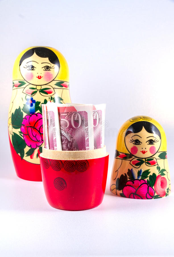 UK Money in Russia hands - £50 pound sterling bank notes in Russian Dolls Matryoshka. royalty free stock photos