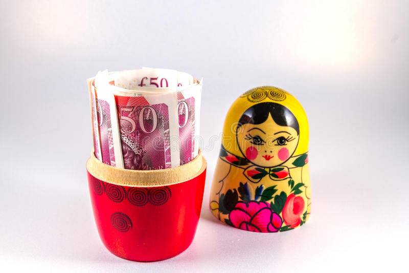 UK Money in Russia hands - £50 pound sterling bank notes in Russian Dolls Matryoshka. stock photos