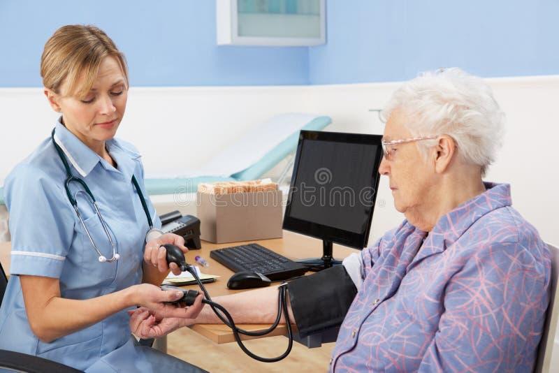 Uk-sjuksköterska som tar höga kvinna blodtryck royaltyfria foton