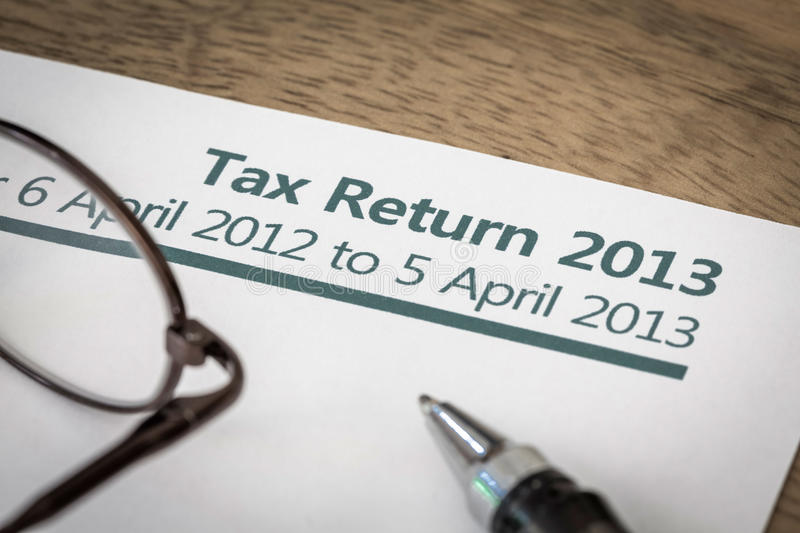 UK tax return 2013. UK Income tax return form for 2013 on a desk with pen and glasses stock image