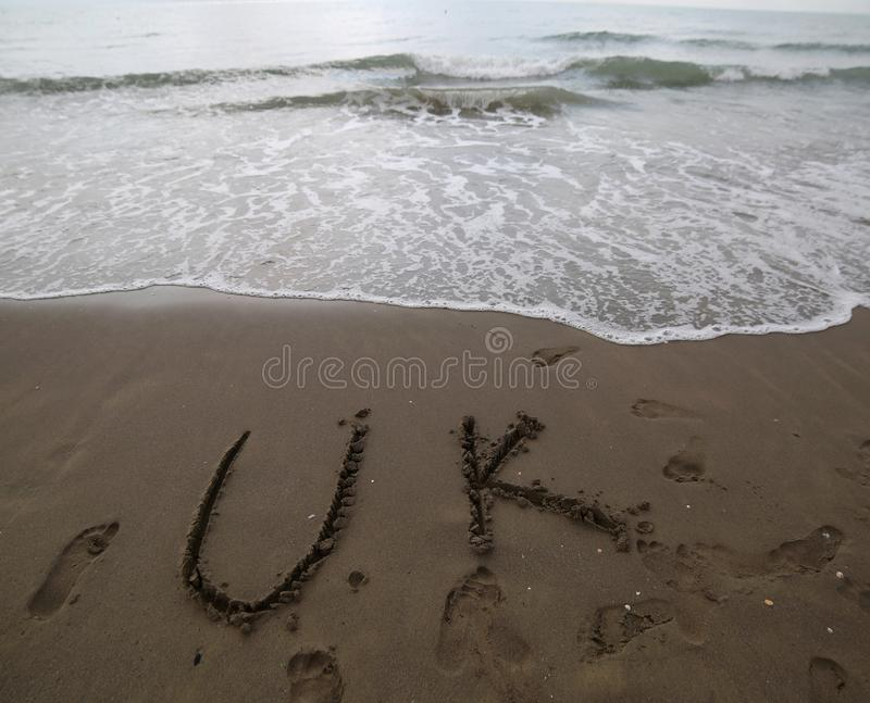 UK text written on the sand of the beach near the sea royalty free stock images