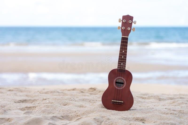 Ukelele de la guitarra puesto en la playa de la arena Opini?n del mar durante d3ia con el fondo del cielo azul Concepto de la est imagen de archivo