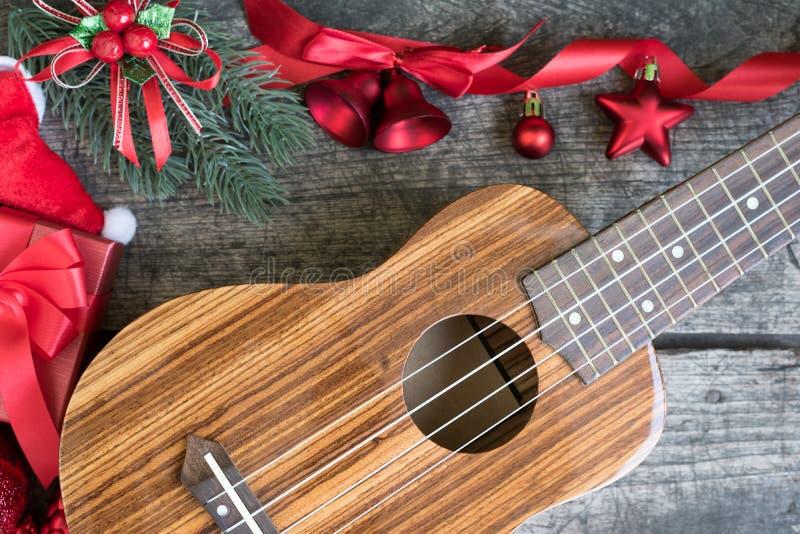 Ukelele en la tabla de madera con el ornamento rojo de la Navidad fotos de archivo libres de regalías