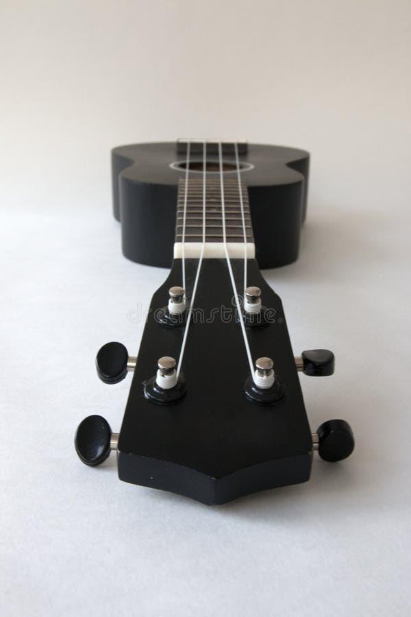 Ukelele, kleine zwarte gitaar, op een witte achtergrond stock afbeelding