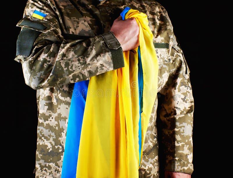 Ukraińscy żołnierzy chwyty w jego ręce błękitna flaga stan, naciskał jego rękę jego klatka piersiowa zdjęcia stock
