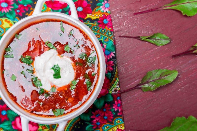Ukraińscy tradycyjni barszcze Rosyjska jarska czerwona polewka w białym pucharze na czerwonym drewnianym tle Odgórny widok Borsch zdjęcia royalty free