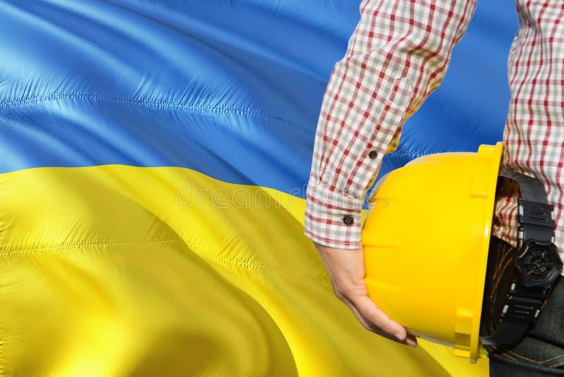 Ukraiński inżynier trzyma żółtego zbawczego hełm z machać Ukraina chorągwianego tło Budowy i budynku poj?cie zdjęcia stock