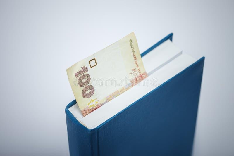 Ukraiński pieniądze bookmark w książce obraz royalty free