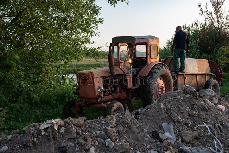 Ukraina, Czerniowce, 10 08 2019 Stary czerwony ciągnik ze zbiornikiem niedaleko jeziora, człowiek rolnik w ubraniach roboczych st fotografia stock