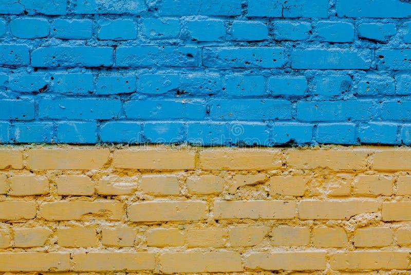 Ukraina flaga malował na starej ścianie z cegieł, tło błękitna ściana z cegieł obraz stock
