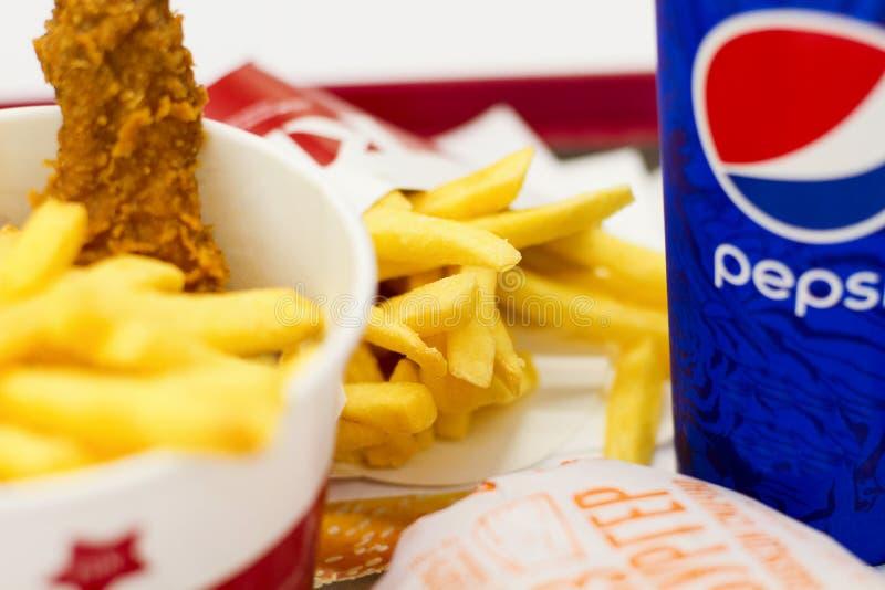 Ukraina Kiev, 05 13 2018: Läcker snabbmat i supermarket KFC stekte chiken, franska småfiskar, ostburgaren McDonalds och pepsi _ fotografering för bildbyråer