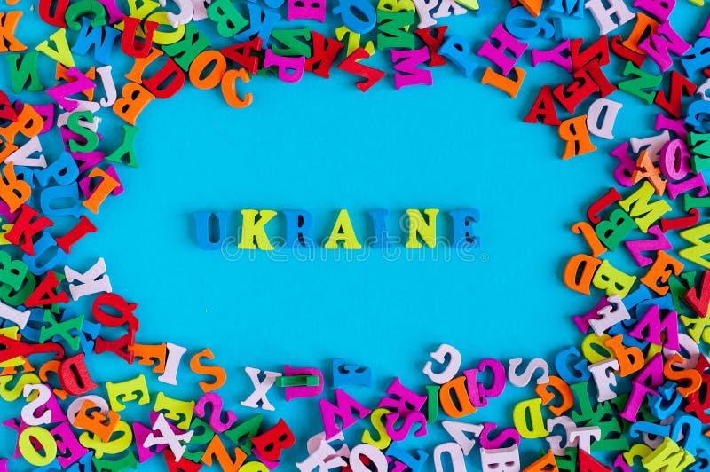 UKRAINA - ord som komponeras av små kulöra bokstäver på blå bakgrundsfithram av många liten bokstav 2017 år arkivbilder