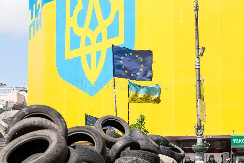 Ukrainare och den europeiska flaggan på barrikaderna av gummihjul i Kiev på självständighet kvadrerar arkivbilder