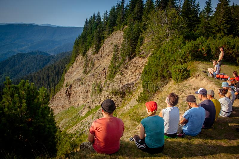 Ukraine, Carpathians - August 27, 2017. A group of tourists on v. Acation at the edge of the mountain royalty free stock photo