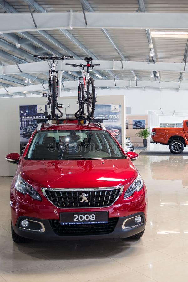 Ukraine, Cherkasy, May 2019. New red family car Peugeot 2008 with a mount on the roof for bicycles in the car dealership. Two stock photos