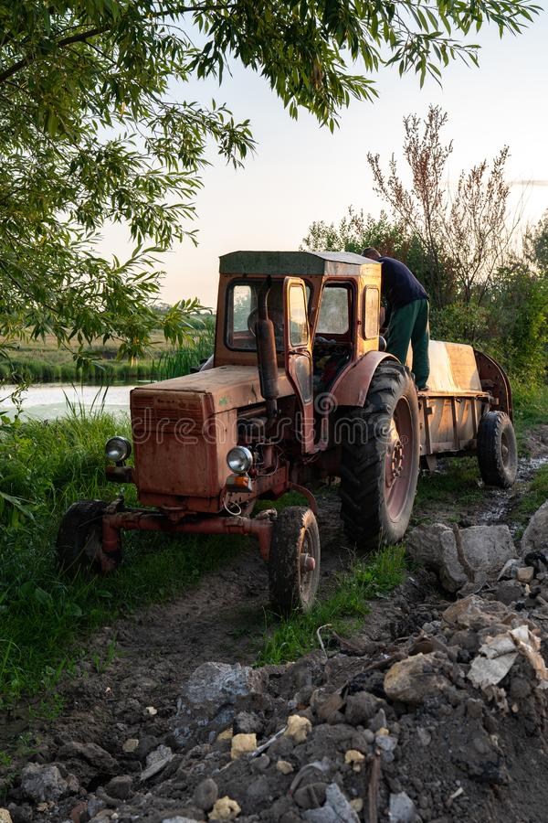 Ukraine, Chernivtsi, 10/08/2019 Old red tractor with tank near the lake, man farmer in work clothes standing on the. Barrel sprayer, gardener`s life concept royalty free stock photo