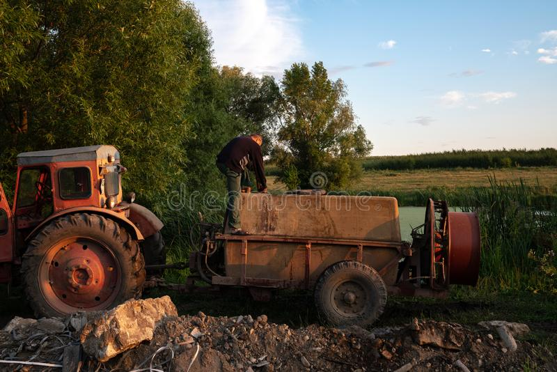 Ukraine, Chernivtsi, 10 08 2019 Old red tractor with tank standing near the lake, man in work clothes fills the barrel. Sprayer with water, gardener life royalty free stock photo