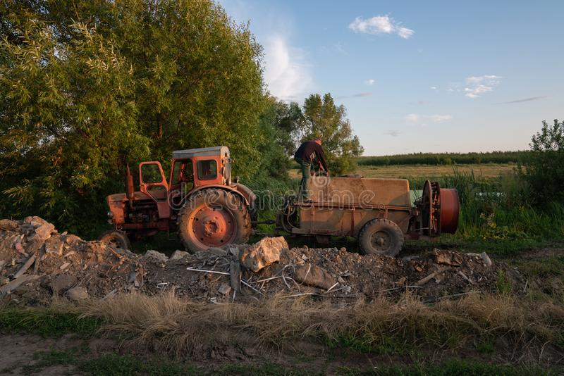 Ukraine, Chernivtsi, 10 08 2019 Old red tractor with tank standing near the lake, man in work clothes fills the barrel. Sprayer with water, gardener life stock photo