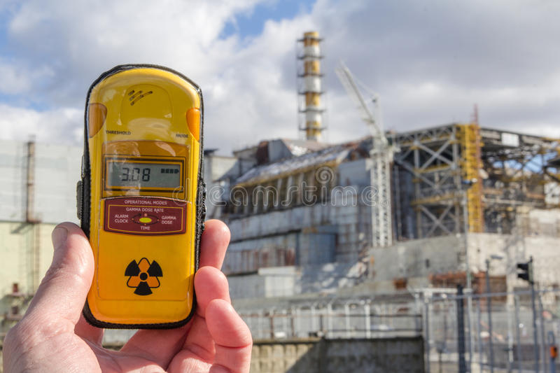 UKRAINE. Chernobyl Exclusion Zone. - 2016.03.19. Dosimeter and Nuclear Power Plant on the background. Chernobyl Nuclear Power Plant and shelter facility. Front royalty free stock image