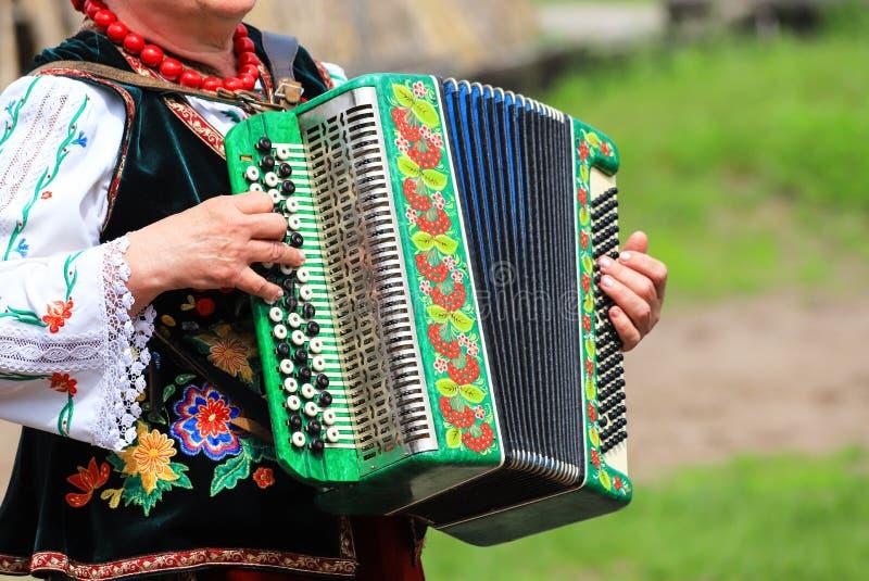 ukraine En äldre kvinna i den ukrainska dräkten spelar dragspelet på den etniska festivalen i Petrikovka arkivfoton