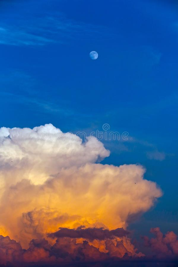 Ukraine, Kiev. The blue sky with the moon and the approaching cloud. The blue sky with the moon and the approaching cloud. Day Blue sky and white moon stock image