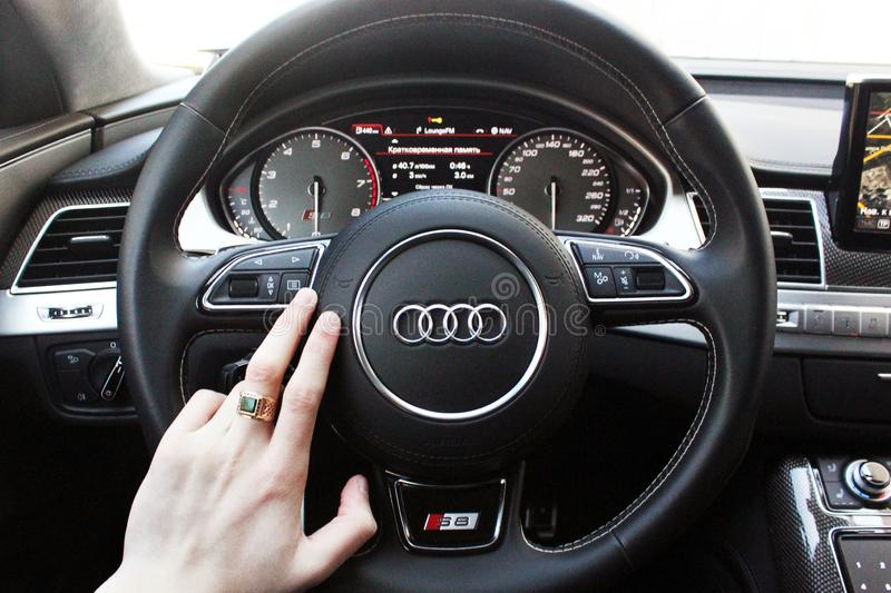 Ukraine, Kiev. March 20, 2015. A man holds the steering wheel of a luxury car. Gold ring on his hand. Audi S8 stock images