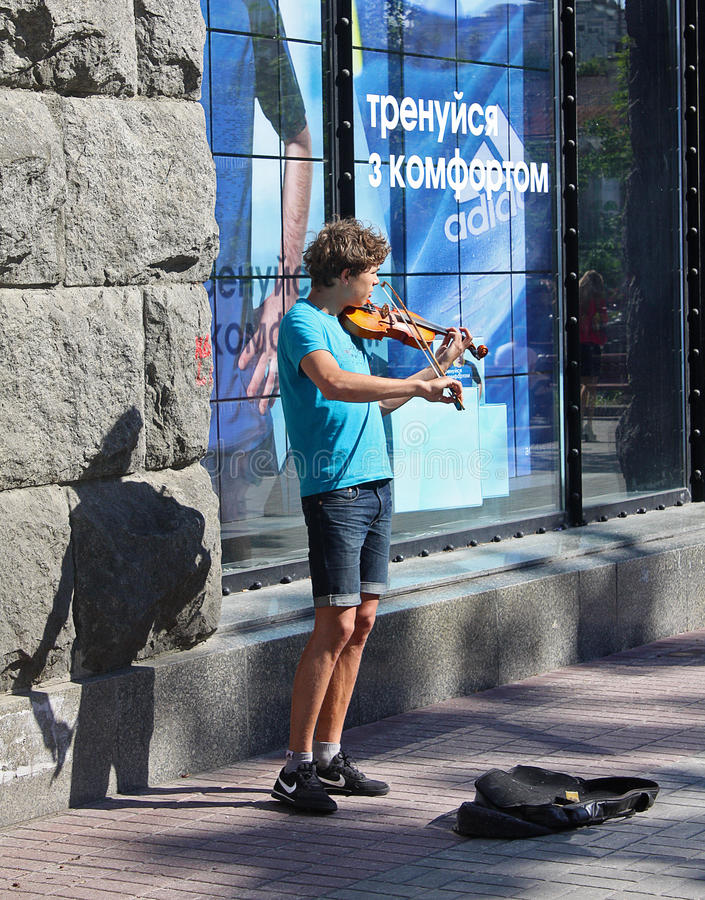 UKRAINE, KIEV - May 27,2013: Young violinist playing on the street Khreschatyk for passers royalty free stock photo