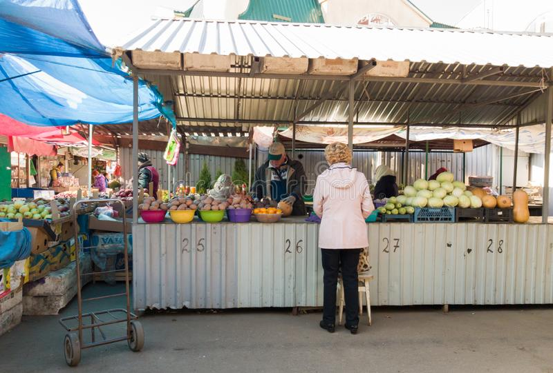 Ukraine, Kiev - October 1, 2019: Farmers food market with a variety of organic vegetables. The seller serves and communicates with. Customers. Counter, kiosk in stock image