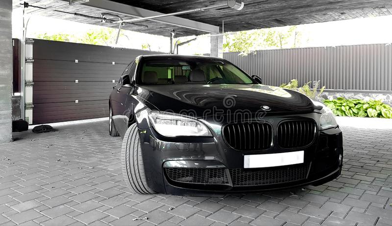 Ukraine, Kiev - September 12, 2019: A new luxury BMW VIP sedan in black and gray is parked in front of the garage door of the royalty free stock photos