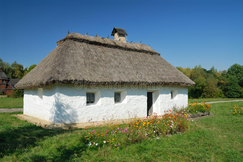 Ukraine. Kiev. White clay house with a thatch. Against a background of flowers and blue sky royalty free stock photography