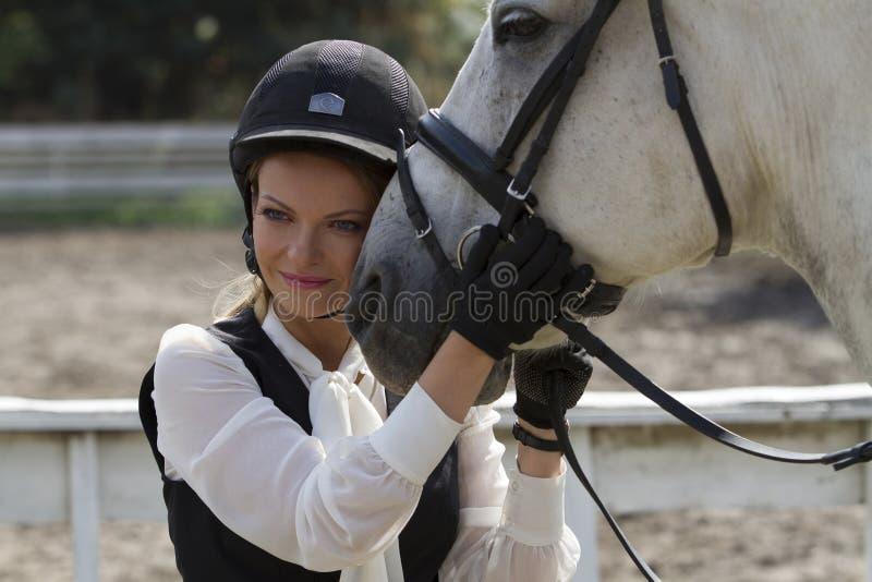Ukraine, Kiew Das Reitermädchen umarmt den Pferd-` s Kopf lizenzfreies stockfoto
