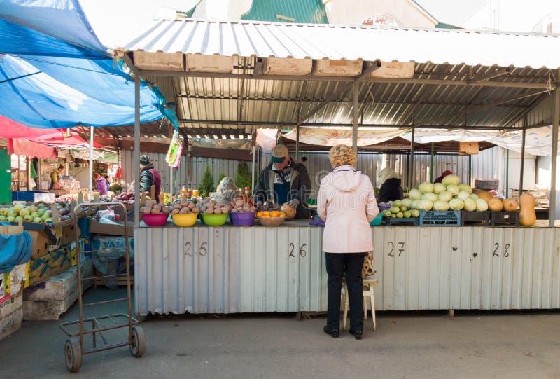 Ukraine, Kiew - 1. Oktober 2019: Lebensmittelmarkt für Landwirte mit einer Vielzahl von ökologischem Gemüse Der Verkäufer bedient stockbild