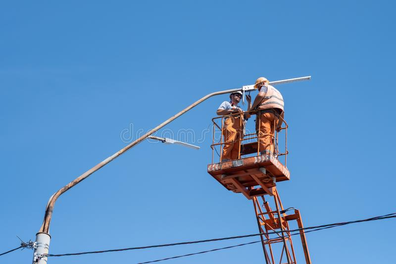 City Workers electrician installing a bulb into a street lamp. Profession that provides comfort, electricity in cities stock photos